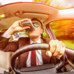 Man drinking out of a flask while drunk driving