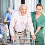Nurse assisting a man in nursing home facility