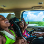 Brazilian girls singing and laughing sitting in backseat in car
