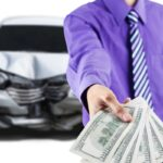 Man with broken car shows dollar money