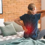 Young man suffering from back pain at home