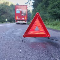 Red warning triangle on a road with a broken down truck.