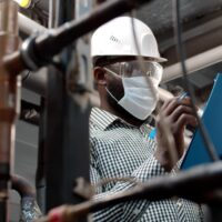 African mechanical supervisor in safety mask doing inspection on plant.