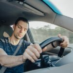 Fatigue of sleeping driver driving at speed while holding wheel while driving on highway in forest. Front view of exhausted man